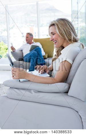 Happy woman with laptop and man using technology at home