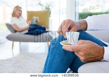 Midsection of man having coffee at home with woman in background