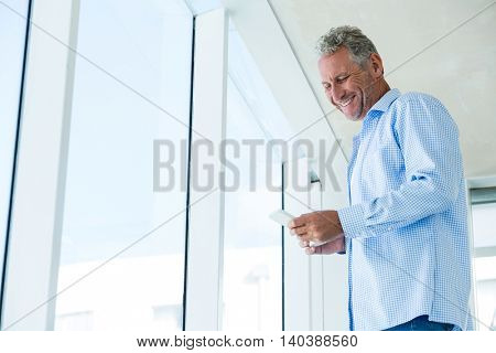 Low angle view of smiling man using phone while standing at home