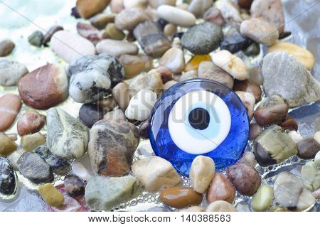 Colorful pebbles on the beach with turkish evil eye glass bead. Background with color stones on the sea and amulet. Sea shore bright stones pebble gravel boulder