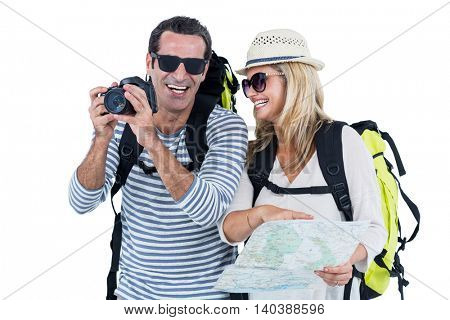 Cheerful mid adult couple carrying luggage against white background