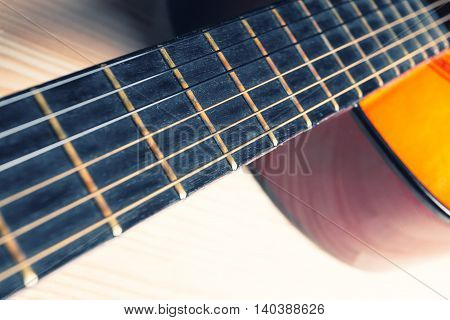 Neck strings sound box of a yellow and orange guitar. Music instrument. Light wooden background.