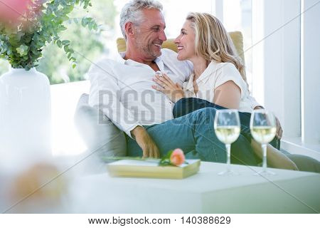 Romantic couple sitting on armchair at home