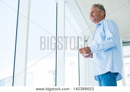 Low angle view of mature man holding phone while standing at home