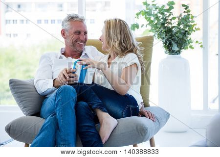 Happy mature couple with gift box at home