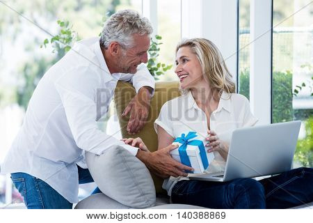Happy man giving gift to woman with laptop at home