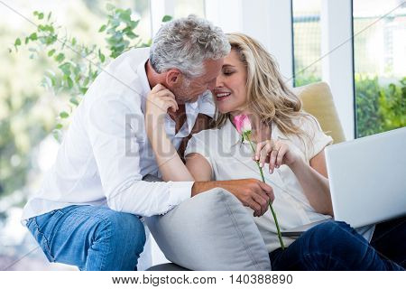 Romantic mature man giving rose to woman at home