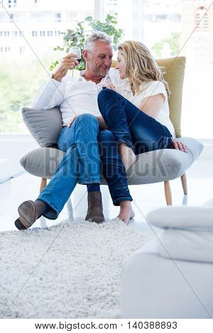 Romantic mature couple with red wine while sitting at home