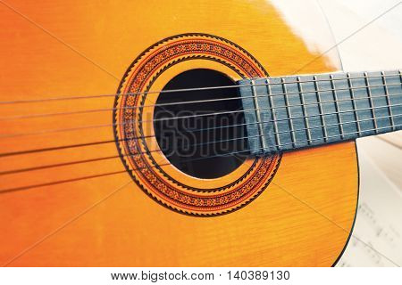 Yellow and oragne classic guitar with strings. Musical instrument.