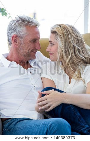 Smart mature couple sitting face to face at home