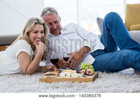 Happy couple with red wine and food while lying on rug at home