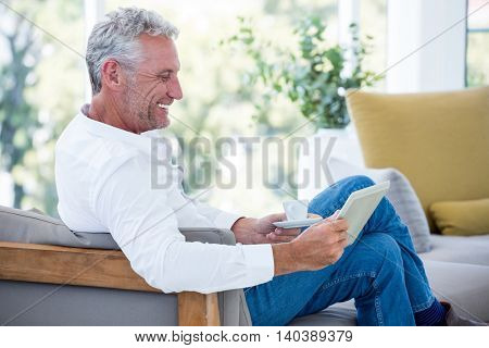 Side view of smiling mature man using tablet at home