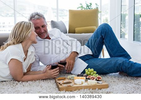 Romantic couple with red wine and food while lying on rug at home