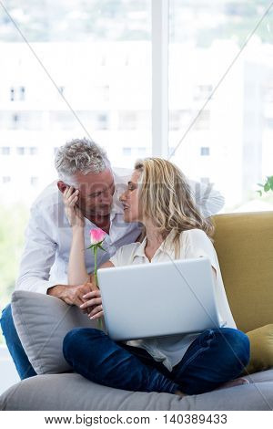 Romantic mature couple with rose and laptop at home