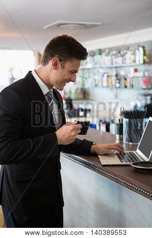 Businessman holding a cup of coffee while using laptop in restaurant