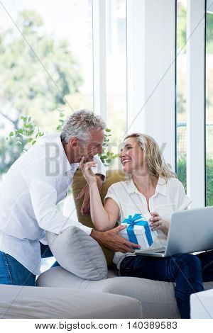 Romantic couple with gift and laptop at home