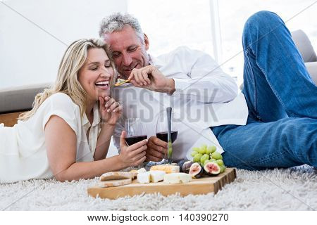 Romantic man feeding woman while lying on rug at home