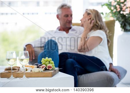 White wine and food on table with couple in background