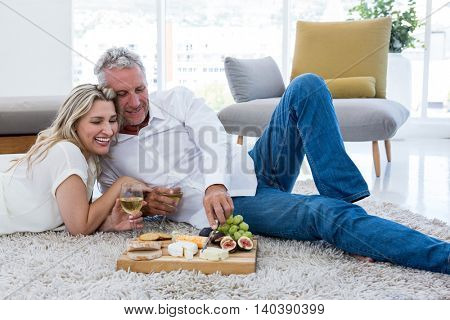 Smiling couple having food while lying on rug at home