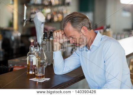 Tired man leaning his elbow on the bar counter in restaurant