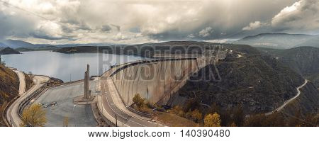 River And Massive Dam Surrounded By Mountains Wide Angle Land Shot View Photo