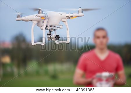 Man controls a quadrocopter. Selective focus on drone, men is blurred.