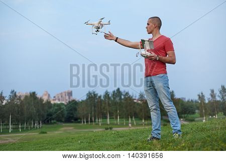 Young man controls a quadrocopter in park.