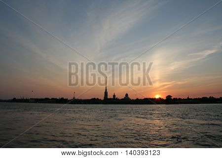 Towers and pillars of fortress and sunset on Neva river