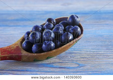 Close up photo of blueberries in the wooden spoon. Fresh ripe juicy bilberries bright autumn colorful background. Concept for healthy diet with berries. Selective Soft focus