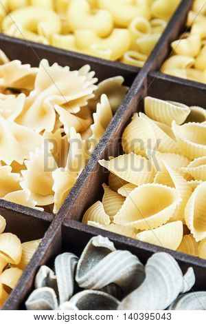 pasta assortment background. Pasta in a wooden box. Italian pasta of different colors. focus on the paste in the middle of the frame