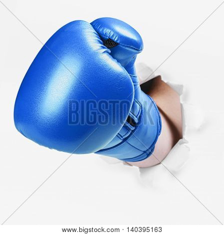 Hand in a blue boxing glove broke through the paper wall. Place an empty paper for your text
