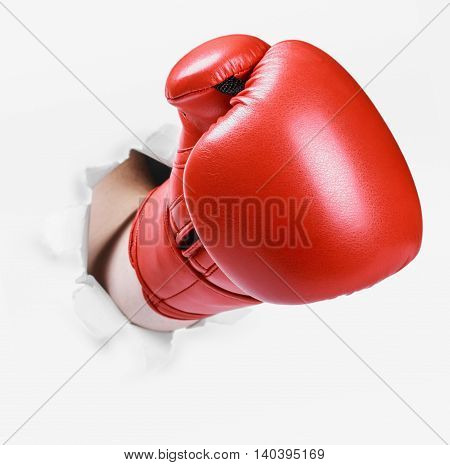 Hand in a red boxing glove broke through the paper wall. Place an empty paper for your text