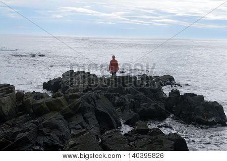 A woman standing alone on a rock jetty overlooking the North Atlantic Ocean