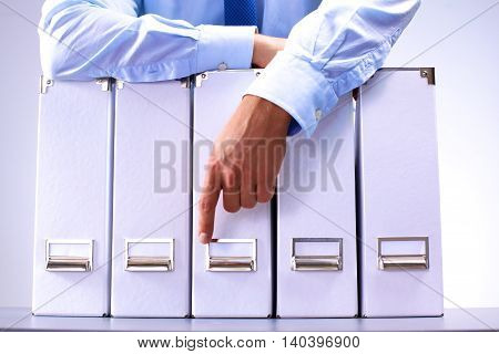 businessman standing over a folder with documents.