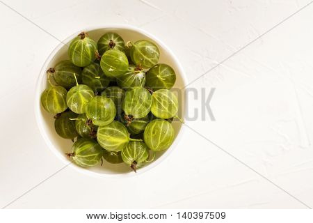Bowl of green gooseberry. Toned image. Top view. Space for text
