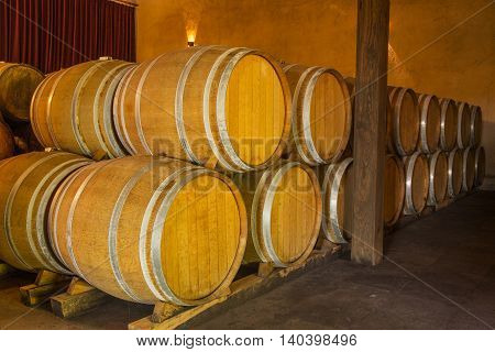 Wine barrels stacked in the old cellar of the winery.