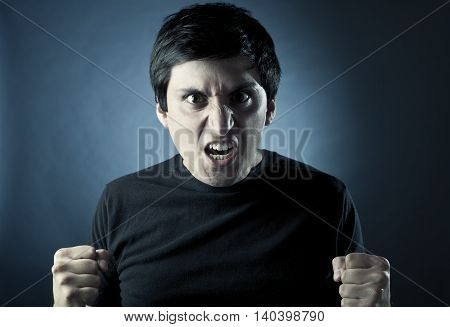 A portrait of angry young man with black background