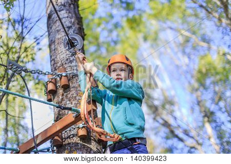 boy struggling with fear of heights. child intends to go through an obstacle course in a ropes course attraction. kid climbing high wire park