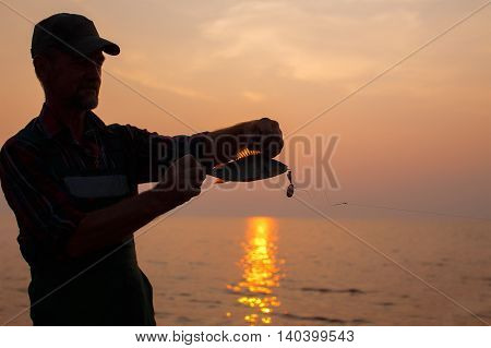 fisherman shows catch in the light of sunset. silhouette of a fisherman with a fish in his hands. the rays of the setting sun beautifully illuminate the fish fin