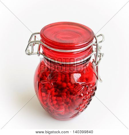 Red jar for spices on a white background.