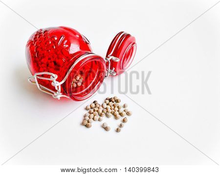 Pepper in red jar on a white background.