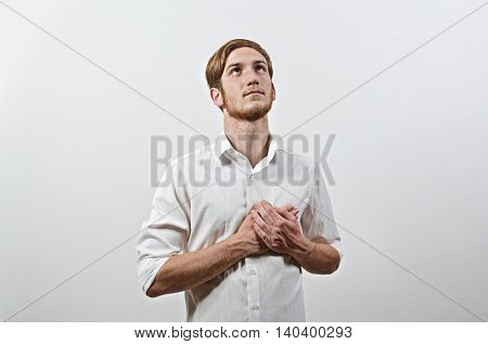 Standing Young Male Adult in White Shirt Listening National Anthem, Hands at Heart. Patriot.