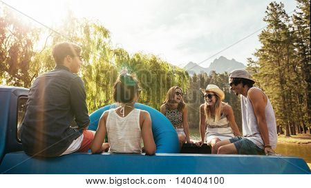 Portrait of smiling young friends going on a holiday. Young men and woman sitting in the back of a pickup truck with inflatable tubes.