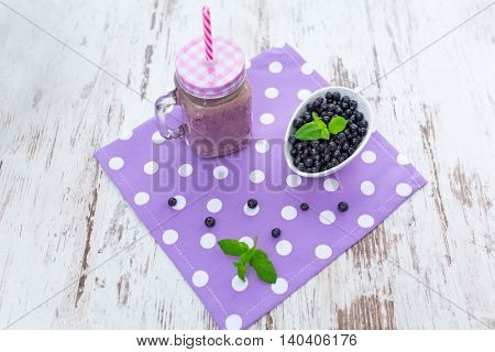 Blueberry smoothie in a glass jar with a straw and bowl of fresh berries