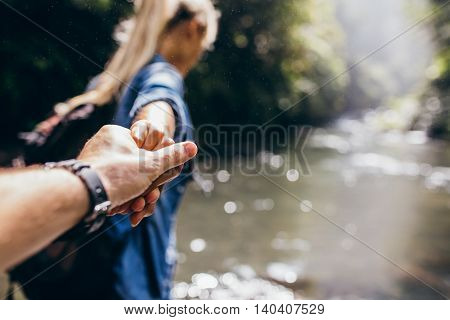 Two Hikers In Nature Crossing The Stream Holding Hands