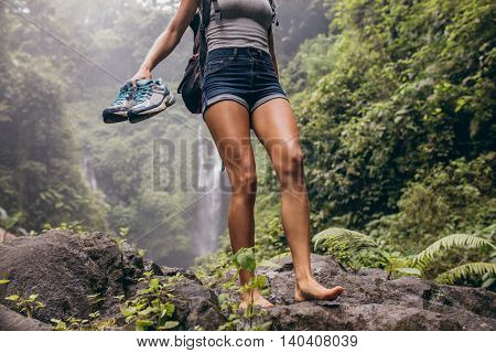 Low angle view of young woman walking down the mountain barefoot. Female hiker walking barefoot on rock with waterfall in background.