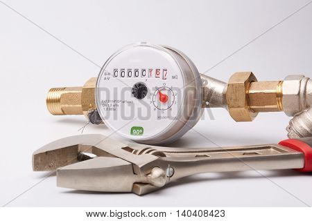 New water meter with fittings and wrench on a white background. Sanitary equipment.