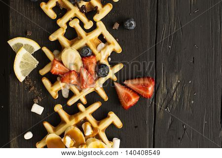 Homemade thick belgium waffles over wooden background. Tasty breakfast concept. Selective focus