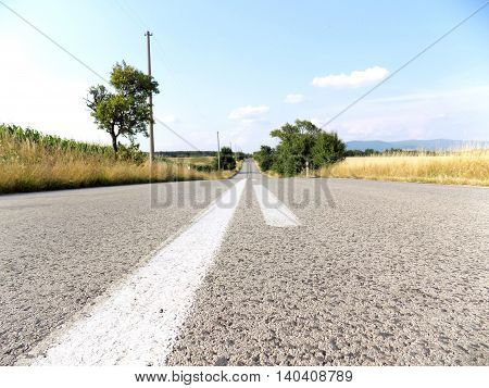 Asphalt speedway road between fields during day