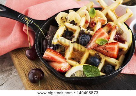 Homemade freshly baked waffles with different toppings in an iron skillet. Breakfast concept. Selective focus